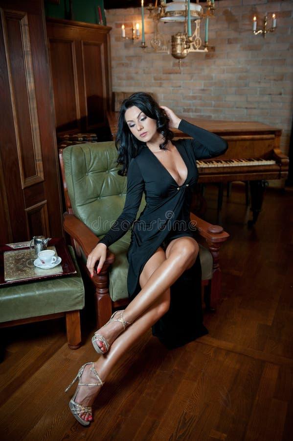 Mooie sexy meisjeszitting op stoel en het ontspannen Portret van donkerbruine vrouw met lange benen die uitdaging vormen Sensueel stock fotografie