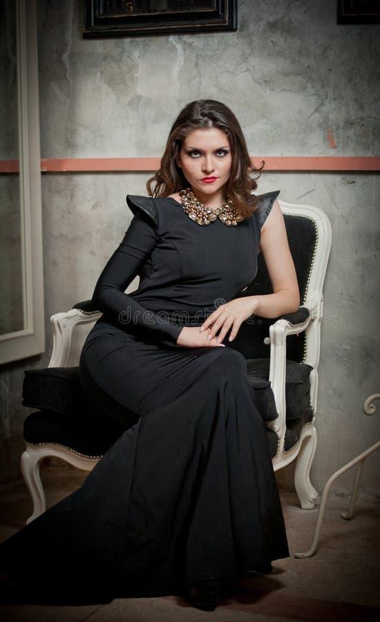 Mooie sexy meisjeszitting op stoel en het ontspannen Portret van donkerbruine vrouw met lange kleding met slechts één koker het s stock foto