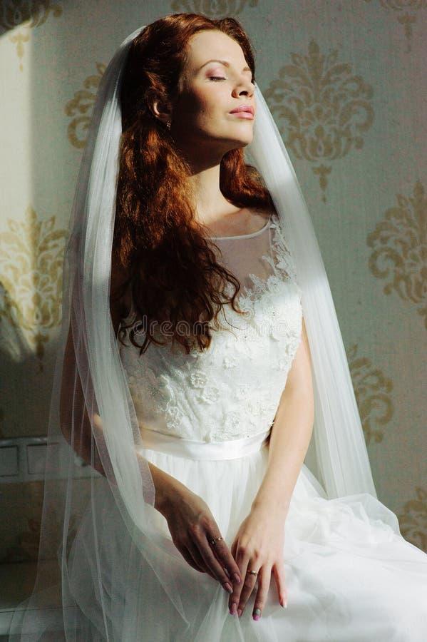 Mooie sexy redhairdame in elegante witte huwelijkskleding Manierportret van model binnen De zitting van de schoonheidsvrouw dicht stock foto