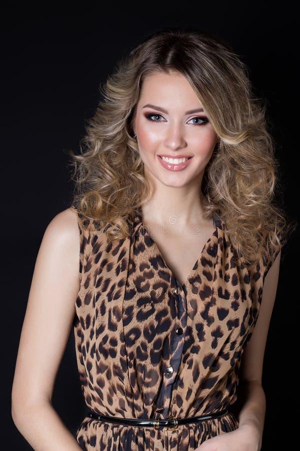 Mooie sexy vrolijke vrouw met helder make-up en avond feestelijk kapsel in de avondjurk van de luipaarddruk op een zwarte backgro royalty-vrije stock fotografie