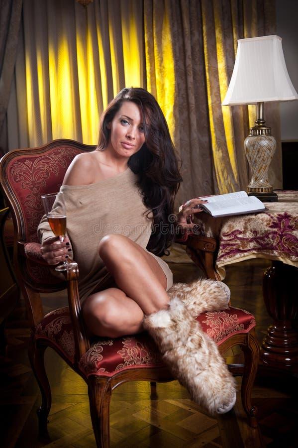 Mooie sexy vrouw die met glas wijn een boekzitting op stoel lezen stock fotografie