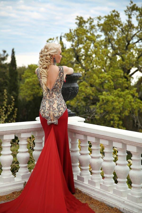 Mooie sexy Vrouw met elegante haarstijl in meermin rode dres stock fotografie