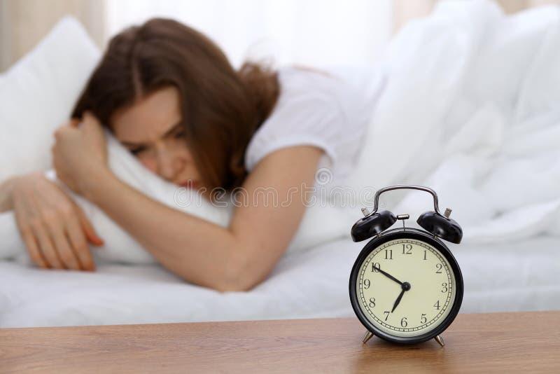 Mooie slaapvrouw die in bed liggen en met wekker proberen te ontwaken Meisje die probleem met vroeg het opstaan hebben royalty-vrije stock foto's