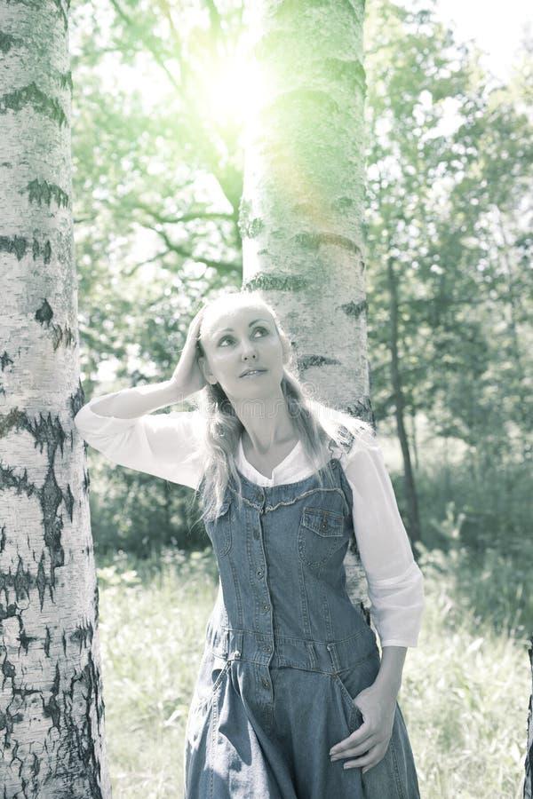 Mooie slanke jonge vrouw in blauwe sundress en een witte blouse dichtbij een berk in zonnige dag, het stemmen royalty-vrije stock afbeeldingen