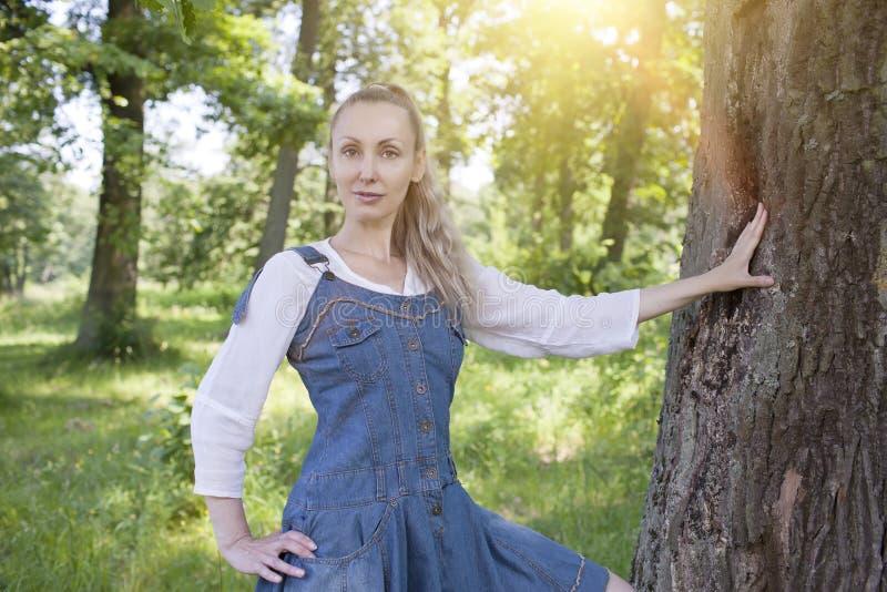Mooie slanke jonge vrouw in blauwe sundress en een witte blouse dichtbij een boomboomstam in het zonnebos stock afbeelding