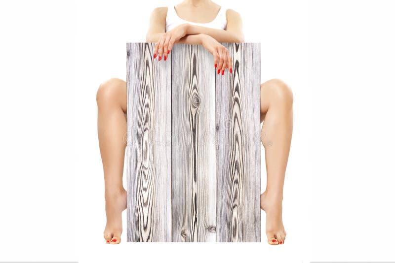 Mooie slanke jonge vrouw, die achter een stuk van laminaat zitten royalty-vrije stock fotografie