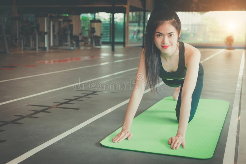 Mooie slanke jonge vrouw die bij gymnastiek rusten Spiermeisje die sportkleding dragen, die op oefeningsmat zitten royalty-vrije stock fotografie