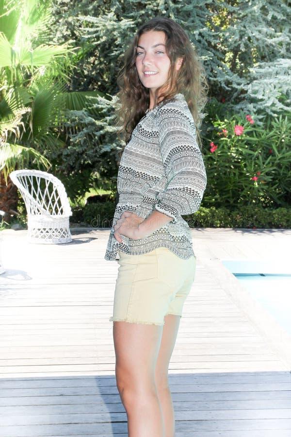 Mooie slanke jonge vrouw die zich dichtbij de pool bevinden royalty-vrije stock foto