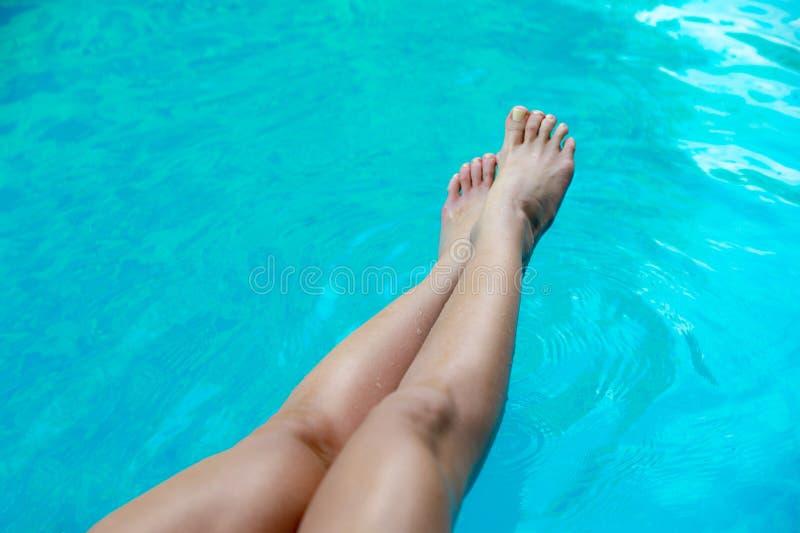 Mooie slanke vrouwen` s benen in zwembad royalty-vrije stock foto's