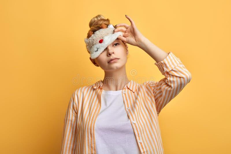 Mooie slaperige dame die eyemask in de ochtend proberen op te stijgen royalty-vrije stock afbeelding