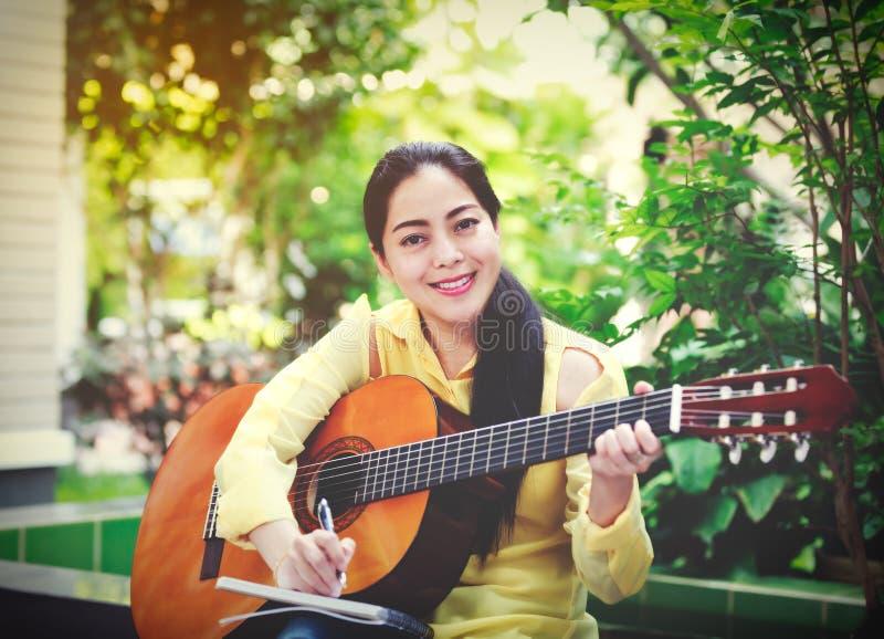 Mooie songwriter die op notadocument schrijven met akoestische gitaar royalty-vrije stock foto's