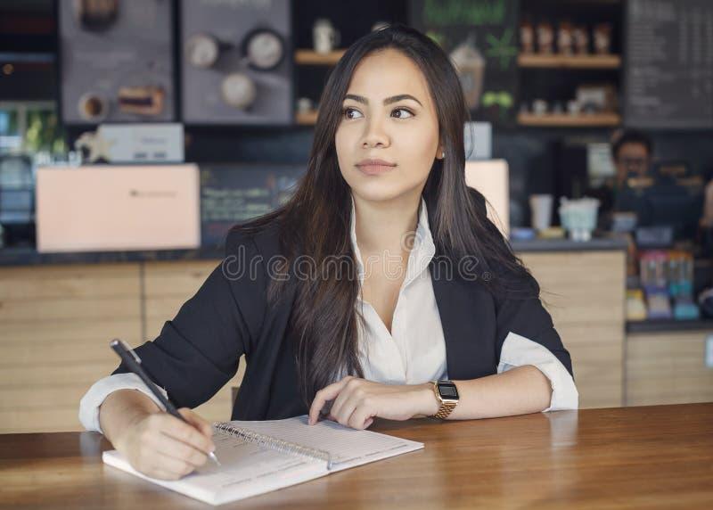 Mooie Spaanse jonge vrouw die in de koffie werken stock foto's