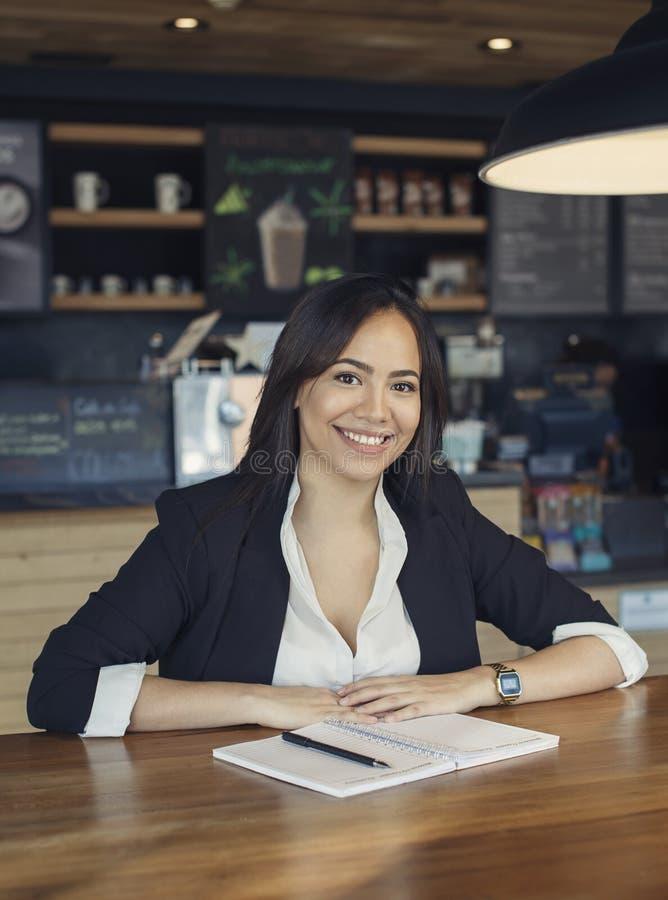 Mooie Spaanse jonge vrouw in kostuum die bij de koffie werken stock foto