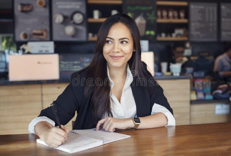 Mooie Spaanse jonge vrouw in kostuum die in de koffie werken royalty-vrije stock foto