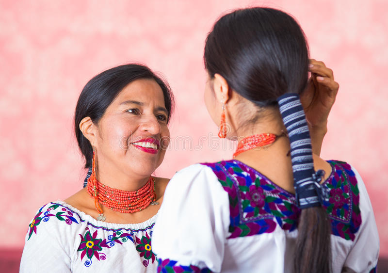 Mooie Spaanse moeder en dochter die traditionele Andesdiekleding dragen, vanuit profielinvalshoek wordt gezien die elkaar onder o royalty-vrije stock foto's