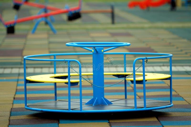 Mooie speelplaats in kleuterschool met zachte bestrating, heldere schommeling, rotonde en bank op zonnige dag Perfecte plaats voo royalty-vrije stock afbeelding
