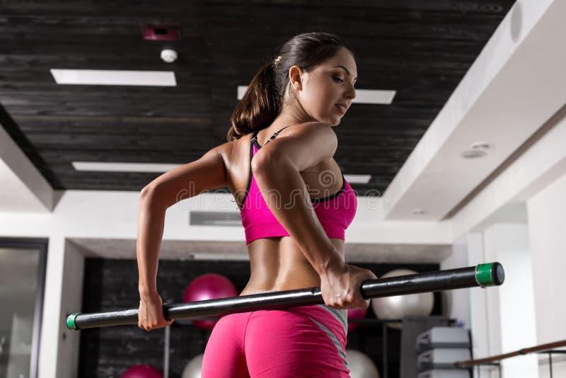 Mooie spiervrouw die oefening met gymnastiek- stok doen bij de gymnastiek royalty-vrije stock foto
