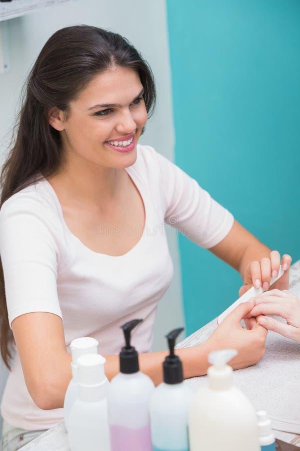 Mooie spijkertechnicus die manicure geven aan klant royalty-vrije stock foto