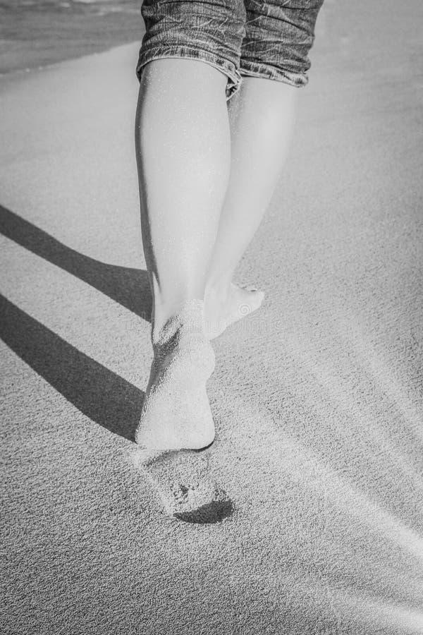 Mooie sporen met voeten dichtbij het overzees op aardachtergrond royalty-vrije stock fotografie