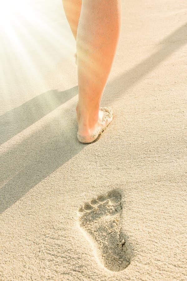 Mooie sporen met voeten dichtbij het overzees op aardachtergrond stock foto