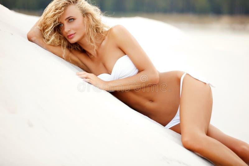 Mooie, sportieve en sexy vrouw die op het strand liggen royalty-vrije stock afbeeldingen