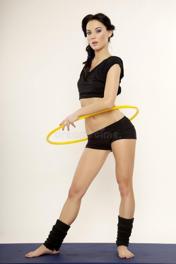 Mooie sportieve vrouw in zwart kledings slank lichaam met hulahoepel stock afbeelding