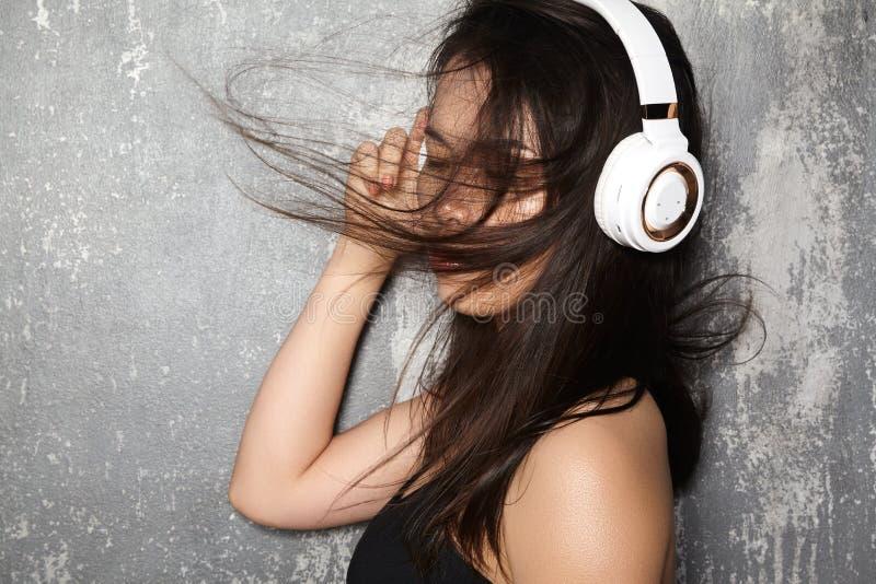Mooie sportvrouw met grote witte hoofdtelefoons Model luisterend de muziek Geschiktheidsportret, perfecte lichaamsvormen royalty-vrije stock afbeelding