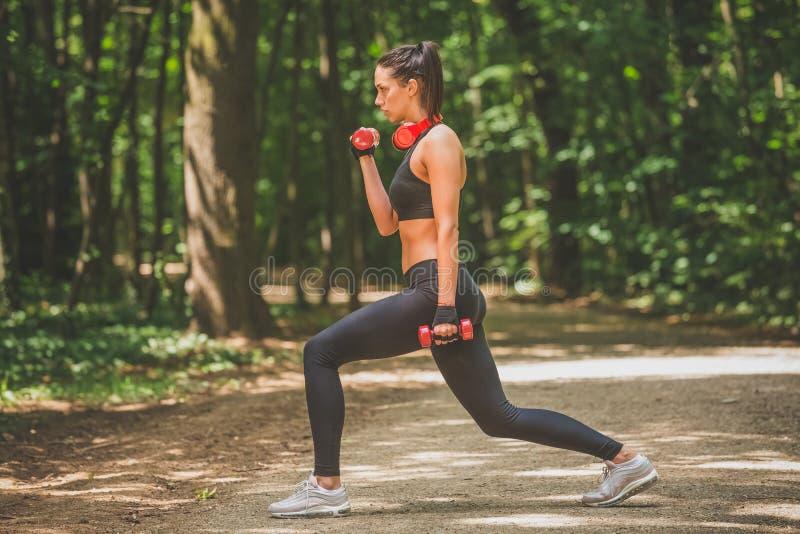 Mooie sportvrouwtraining door kleine gewichten in aard te gebruiken stock afbeelding