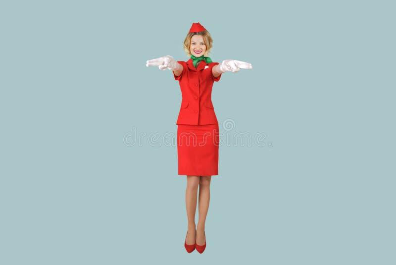 Mooie stewardess die in rode eenvormig op grijze achtergrond dragen royalty-vrije stock afbeelding