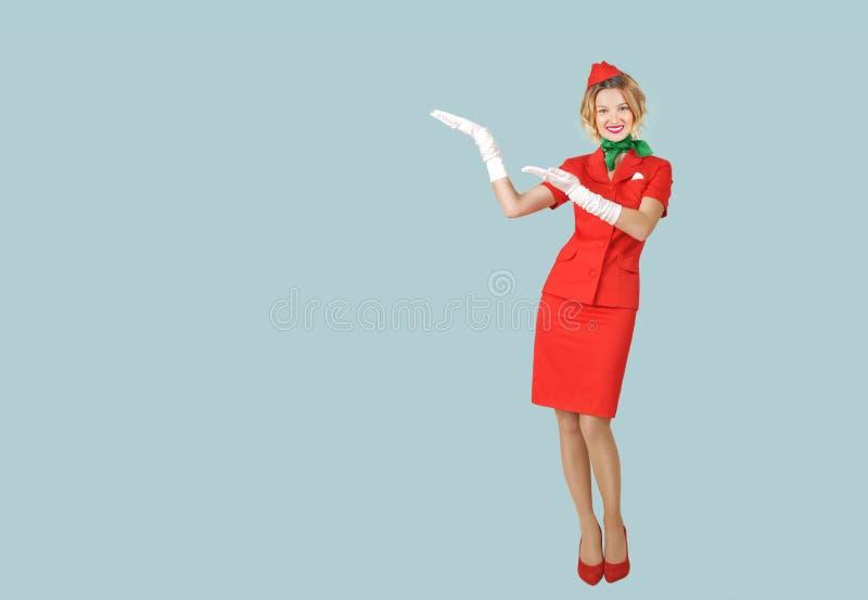 Mooie stewardess die in rode eenvormig op grijze achtergrond dragen stock foto