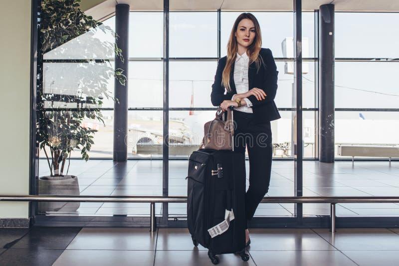 Mooie stewardess die zich in haar uniform met haar zakken klaar voor een vlucht bevinden royalty-vrije stock foto's