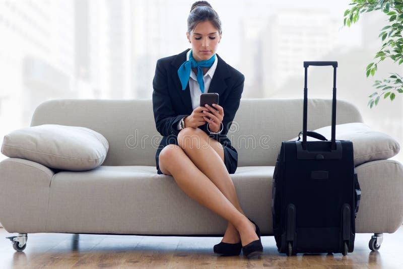 Mooie stewardess in luchthaven met mobiele telefoon royalty-vrije stock foto