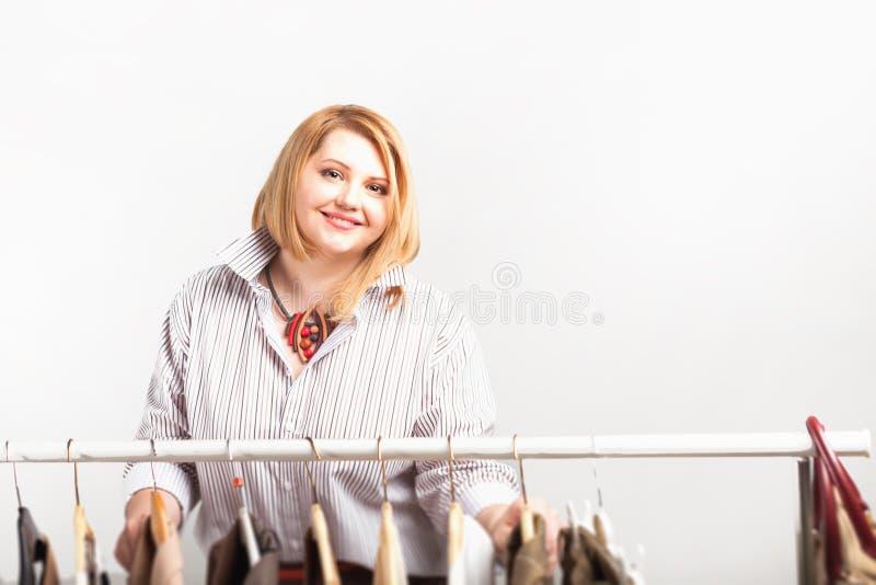 Mooie stilist dichtbij rek met hangers royalty-vrije stock afbeeldingen
