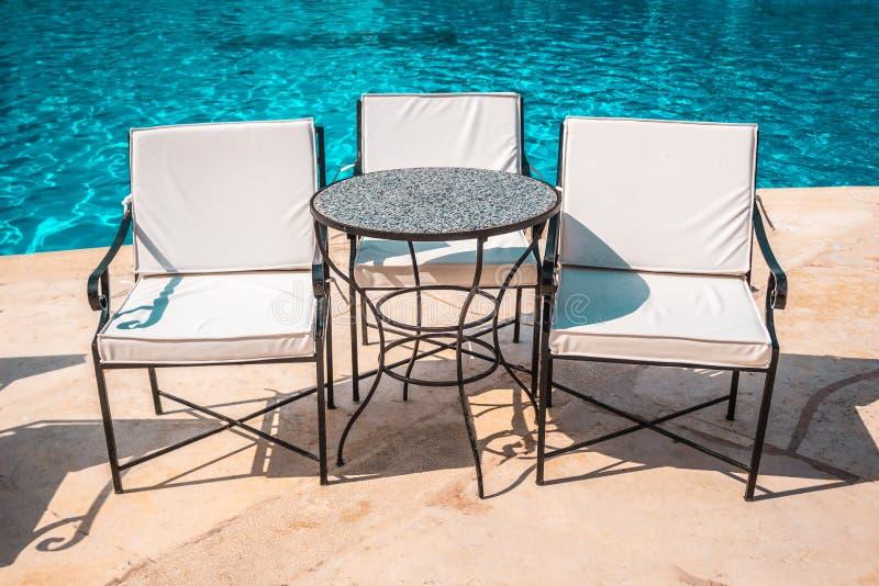Mooie stoelen en een kleine lijst naast de pool royalty-vrije stock foto