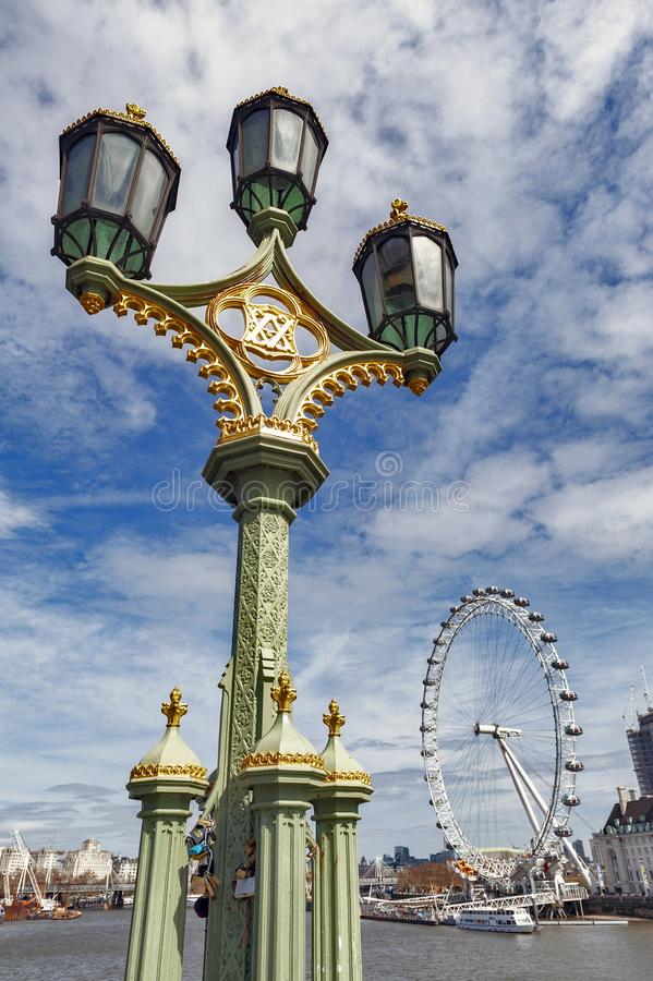 Mooie straatlantaarn op de Brug van Westminster in Londen met het Oog van Londen, populair die oriëntatiepunt van de stad op acht stock fotografie