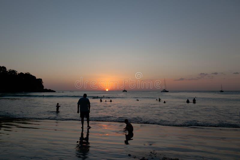 Mooie strandkata phuket in Thailand op puhketeiland Silhouetten van mensen bij zonsondergang In de voorgrond zijn het silhouet va stock afbeelding