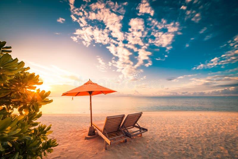Mooie strandzonsondergang met zonbedden en ontspannende stemming stock foto