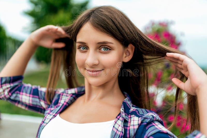 Mooie studente 13-16 jaar oud, in de zomer in het park in de verse lucht Maakt lang haar, gelukkige glimlachen recht royalty-vrije stock afbeeldingen