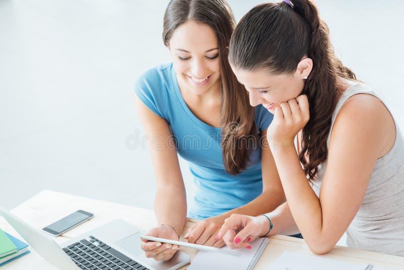 Mooie studenten die een digitale tablet thuis gebruiken stock fotografie