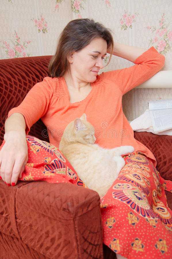 Mooie tatar vrouw op stoel het ontspannen met kat en het lezen magaz stock foto