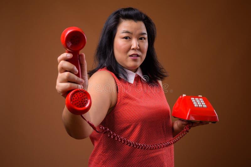 Mooie te zware Aziatische vrouw die oude rode telefoon geven stock foto