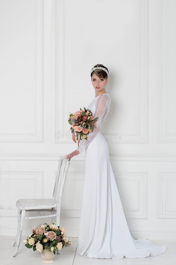 Mooie tedere elegante jonge meisjesbruid in huwelijkskleding met kroon op hoofd in studio op witte achtergrond met boeket in hand royalty-vrije stock foto
