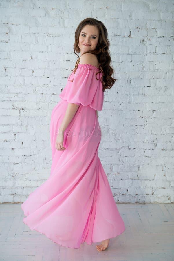 Mooie tedere zwangere vrouw in roze kleding royalty-vrije stock afbeeldingen