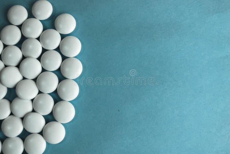 Mooie textuur met witte ronde vlotte medische pillen, vitaminen, antibiotica en exemplaarruimte op een blauwe achtergrond Vlak le stock foto's