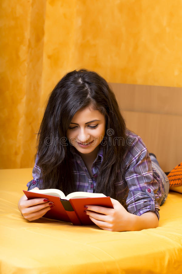 Mooie tiener die in bed liggen en een boek lezen stock afbeeldingen