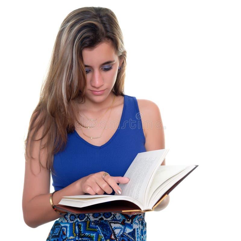 Mooie tiener die die een boek lezen op wit wordt geïsoleerd stock afbeeldingen