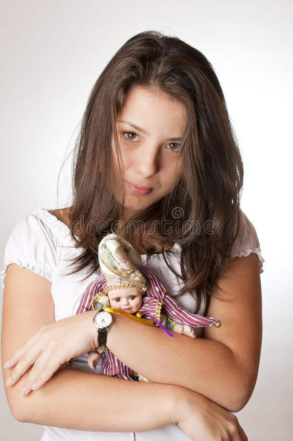 Mooie tiener die een pop in haar wapens houdt stock foto