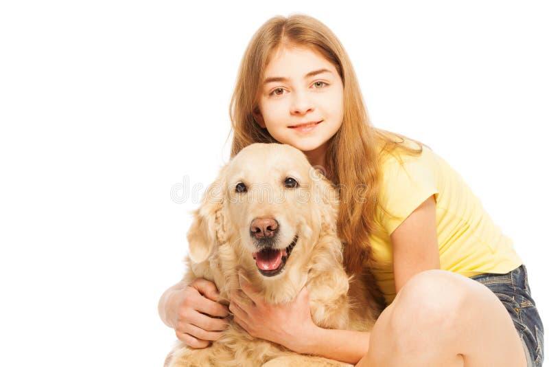 Mooie tiener die Golden retriever koesteren stock foto's
