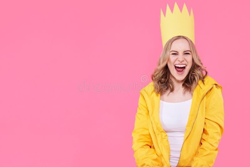 Mooie tiener die in heldere gele jasje en partijhoed met opwinding schreeuwen Het aantrekkelijke koele portret van de vrouwenmani stock fotografie