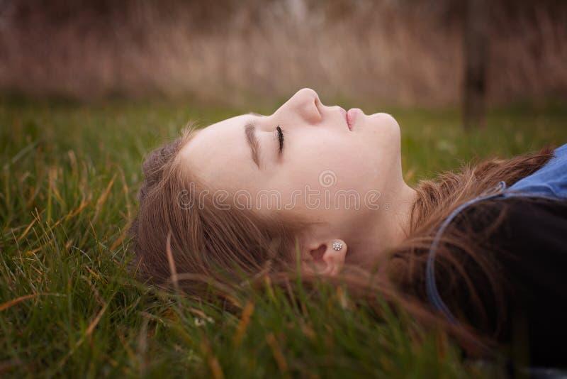 Mooie tiener die op gras met haar gesloten ogen liggen royalty-vrije stock foto's